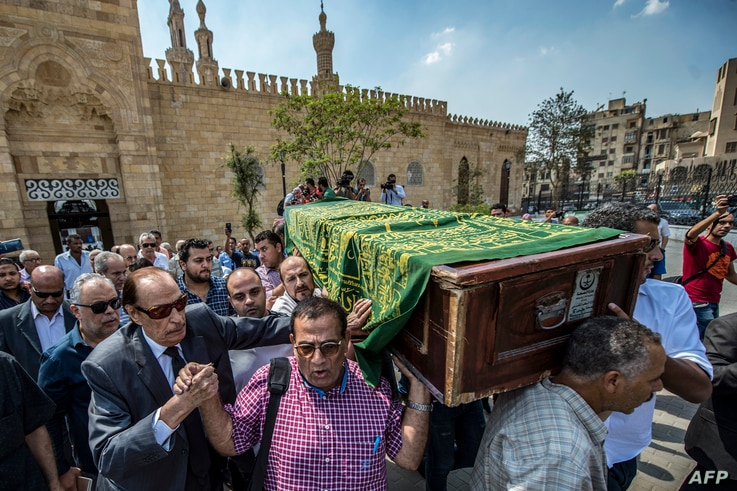 Ashraf Zaki (2nd-L), head of the Egyptian actors syndicate, along with veteran Egyptian actor Ezzat al-Alayli (3rd-L), walk with relatives and friends carrying the coffin of French Egyptian veteran actor Gamil Rateb during his funeral as they exit Al...