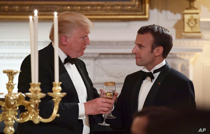 President Donald Trump, left, and French President Emmanuel Macron, right, share a toast during the State Dinner at the White House, April 24, 2018.