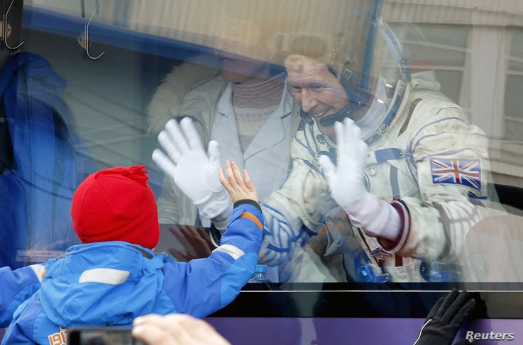 British astronaut Tim Peake, a member of the main crew of the International Space Station, waves to his children from a bus prior the launch of Soyuz TMA-19M space ship, at the Russian leased Baikonur cosmodrome, Kazakhstan, Dec. 15, 2015.