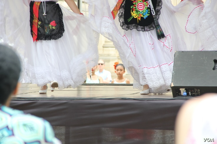 """One of the younger members of Baltimore's """"Bailes de Mi Tierra"""" Mexican folk dance group watches the older girls perform the first dance at the start of the One Journey Festival in support of refugees, Washington, June 2, 2018. (V. Macchi/VOA)"""