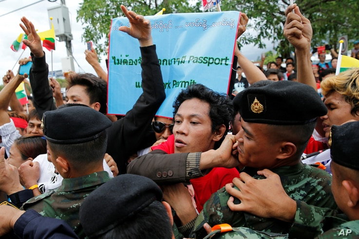 Migrant workers supporting Myanmar Foreign Minister and State Counselor Aung San Suu Kyi push against a line of Thai soldiers to see her past during a meeting at the coastal fishery centre of Samut Sakhon, Thailand, June 23, 2016.