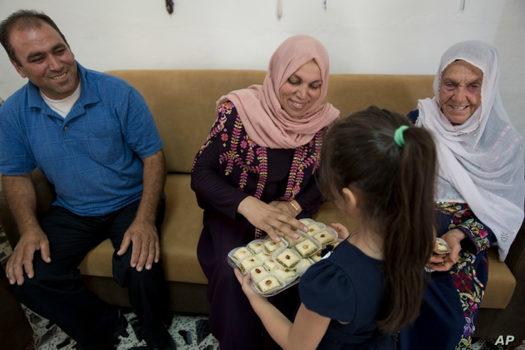 After the Michigan primary victory of Rashida Tlaib on Aug. 7, 2018, a Palestinian girl offers sweets to family members. Aunt Fadwa, center, grandmother Muftiyeh, right and uncle Bassam  celebrate Rashida's U.S. election victory in the West Bank vill...