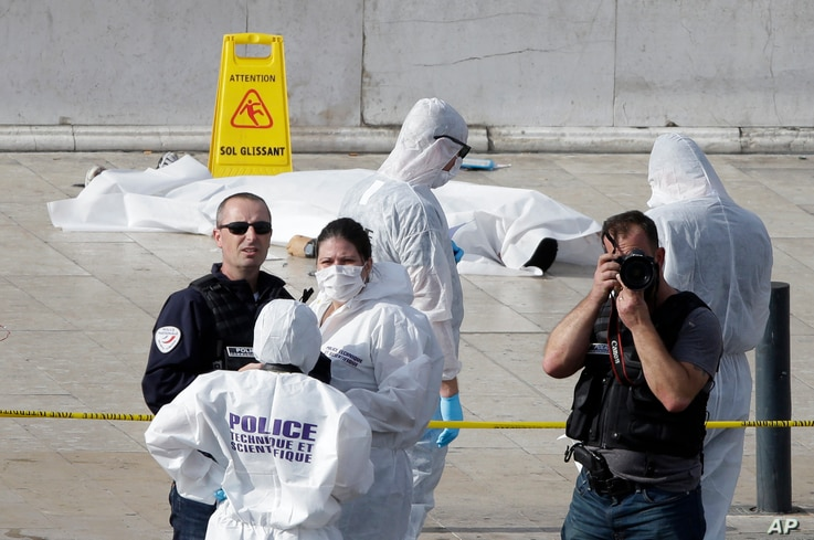 Investigative police officers work by a body covered with white sheet outside Marseille's main train station, in Marseille, southern France,  Oct. 1, 2017.