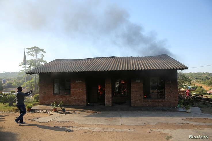 A man uses a cellphone to take pictures of a burning school office in Mashau Dolly village, in South Africa's Limpopo province, May 5, 2016.