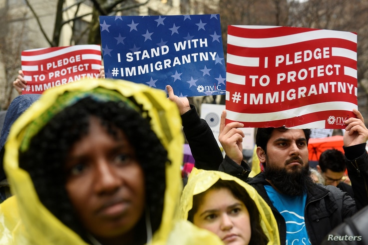 FILE - People hold signs before marching to Trump Tower in a protest organized by the New York Immigration Coalition against President-elect Donald Trump in New York, Dec. 18, 2016.
