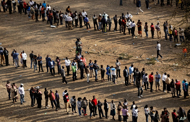 Kenyans queue to cast their votes at dusk at a polling station in downtown Nairobi, Aug. 8, 2017.
