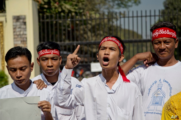 Min Min, second right, rights activist and political prisoner who was released from Insein Prison, shouts slogans demanding the release of all remaining political prisoners outside the prison in Yangon, Myanmar, Jan. 22, 2016.