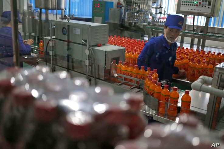 In this Oct. 22, 2018, photo, a worker monitors the production of bottled beverage at Songdowon General Foodstuffs Factory in Wonsan, North Korea.