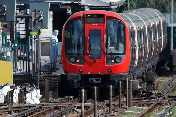 A police forensic officer stands beside the train where an incident happened, that police say they are investigating as a terrorist attack, at Parsons Green subway station in London.