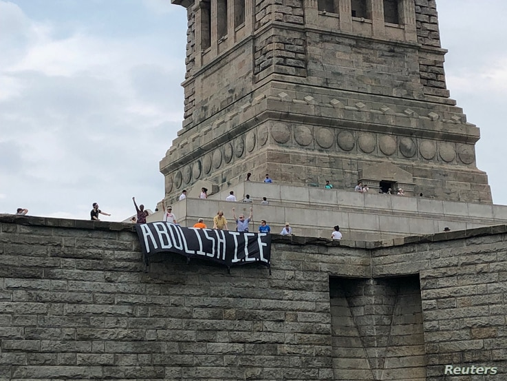 A group called Rise and Resist stages a protest at the Statue of Liberty in New York, July 4, 2018 in this picture obtained from social media.