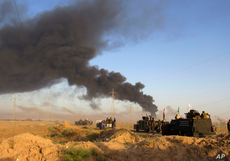 Smoke rises from Islamic State group positions after an airstrike by U.S.-led coalition warplanes in Fallujah, as Iraqi security forces and allied Shiite Popular Mobilization Forces and Sunni tribal fighters, take combat positions outside Fallujah, M...