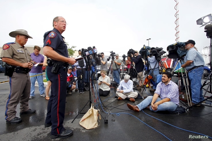 Sgt. Patrick Swanton, second from left, Waco Police Department spokesman, speaks to the media near the Twin Peaks restaurant where nine members of a motorcycle gang were shot and killed Sunday in Waco, Texas, May 19, 2015.