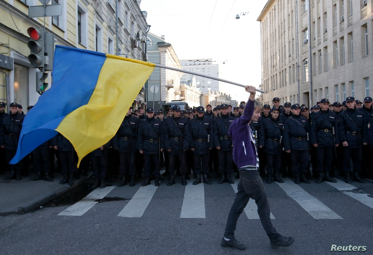 A man with a Ukrainian flag walks past riot police standing guard during an anti-war rally in Moscow, Sept. 21, 2014.