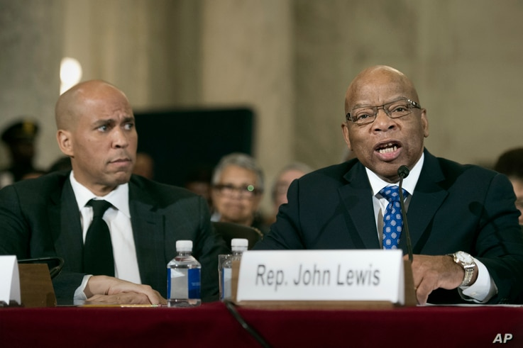 Sen. Cory Session, D-N.J. listens at left as Rep. John Lewis, D-Ga. testifies on Capitol Hill in Washington, Wednesday, Jan. 11, 2017, at the second day of a confirmation hearing for Attorney General-designate, Sen. Jeff Sessions, R-Ala., before the ...