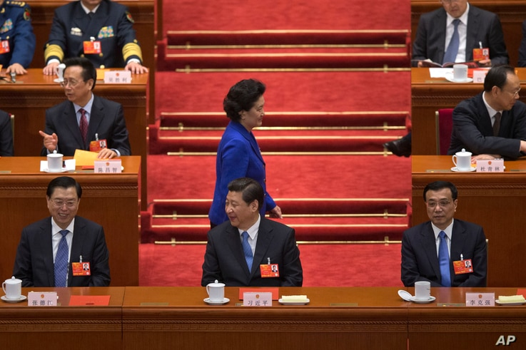 Newly-named Chinese vice Premier Liu Yandong walks past top leaders, including (front row from left to right), National People's Congress chairman Zhang Dejiang and Chinese President Xi Jinping, in Beijing's Great Hall of the People, China, March 16,...