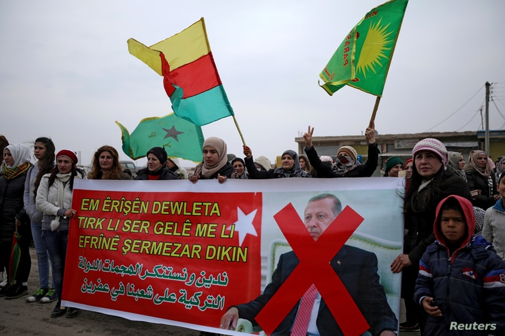 """People hold flags and carry a banner reading, """"We condemn and denounce the attacks of the Turkish government against our people in Afrin,"""" during a protest against Turkish attacks on Afrin, in Hasaka, Syria, Jan. 18, 2018."""