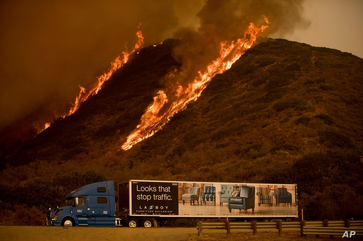 Flames from the Thomas fire burn above a truck on Highway 101 north of Ventura, California, Dec. 6, 2017.