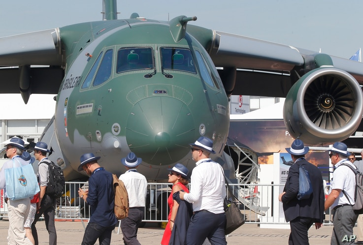 Visitors walk past a Embraer KC-390 military transport aircraft built by Brazilian aerospace manufacturer Embraer at the Paris Air Show, in Le Bourget, east of Paris, June 20, 2017.