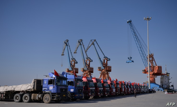 FILE - Chinese trucks stand on a pontoon during the opening of a trade project in Gwadar port, 700 kilometers west of Karachi, Pakistan, Nov. 13, 2016.