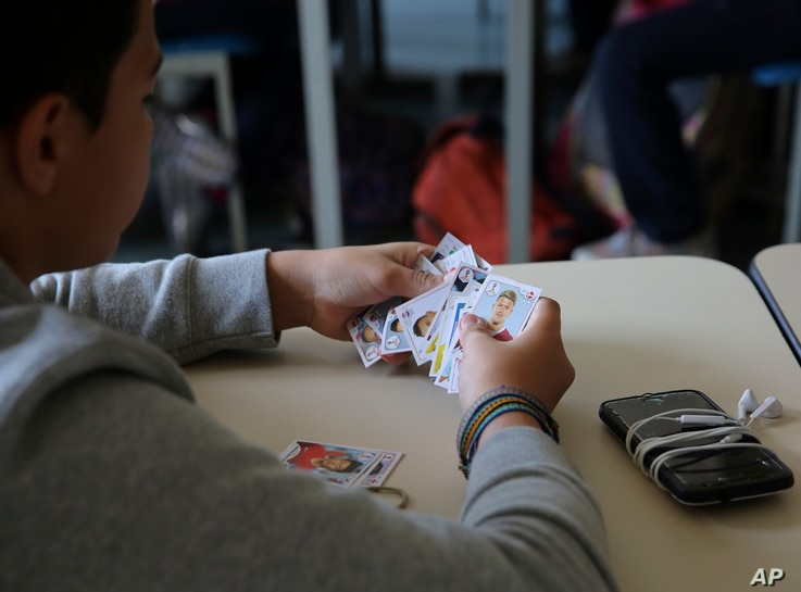 FILE - A student looks at his World Cup stickers in his Portuguese class, in Sao Paulo, Brazil, May 21, 2018.