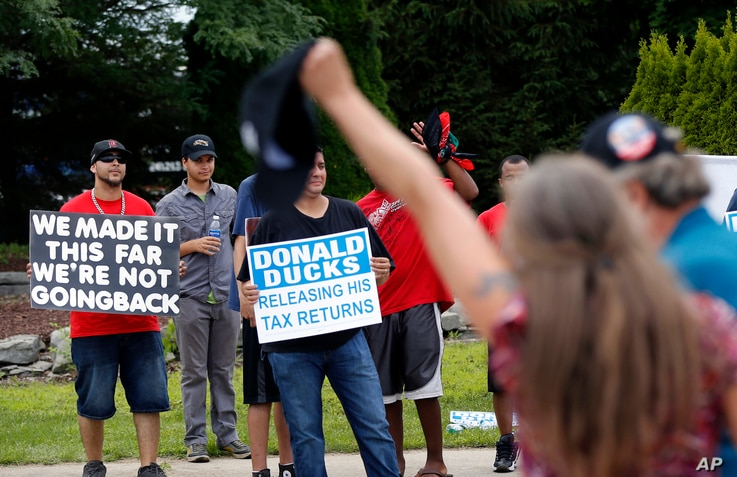 A rally-goer shouts as she passes protesters before Republican presidential candidate Donald Trump speaks at a rally in Dimondale, Mich. Aug. 19, 2016.