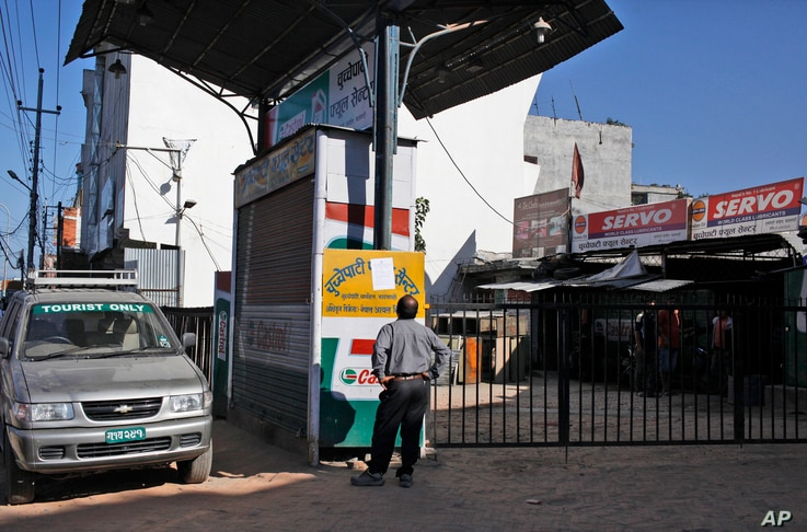 FILE - A Nepalese man reads a notice at a closed fuel station in Kathmandu, Nepal, Oct. 8, 2015. Struggling with a fuel shortage after Indian shipments went on hold, Nepal is looking to import fuel from China.