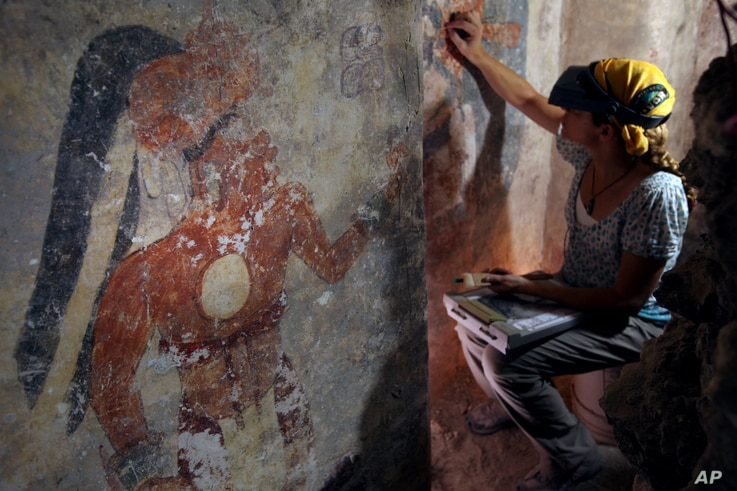 Conservator Angelyn Bass cleans and stabilizes the surface of a wall of a Maya house that dates to the 9th  century A.D. The figure of a man who may have been the town scribe appears on the wall to her left. (Tyrone Turner © 2012 National Geographic...