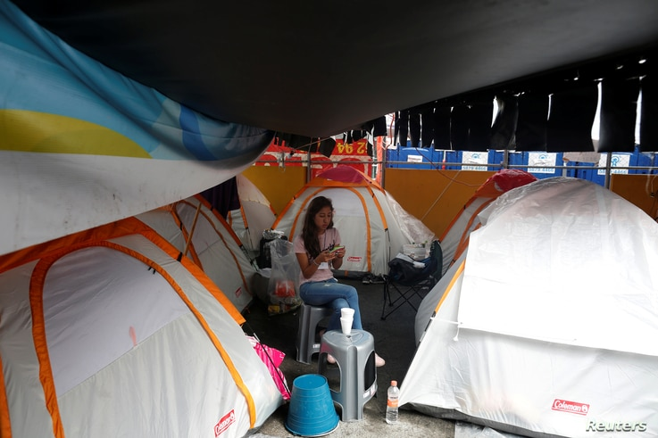 A woman looks at her mobile phone next to her tent in a provincial campsite on a basketball court after her flat was affected by the the earthquake in Mexico City, Mexico, Sept. 25, 2017.