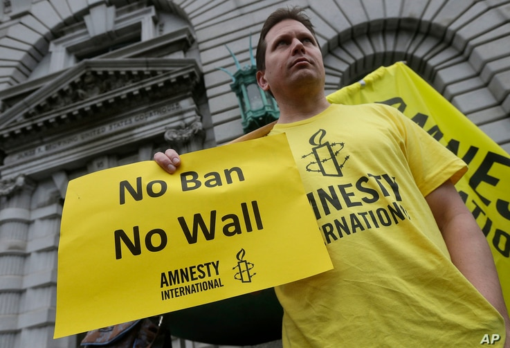 William Butkus of Amnesty International holds up a sign outside of the 9th U.S. Circuit Court of Appeals in San Francisco,  Feb. 7, 2017.