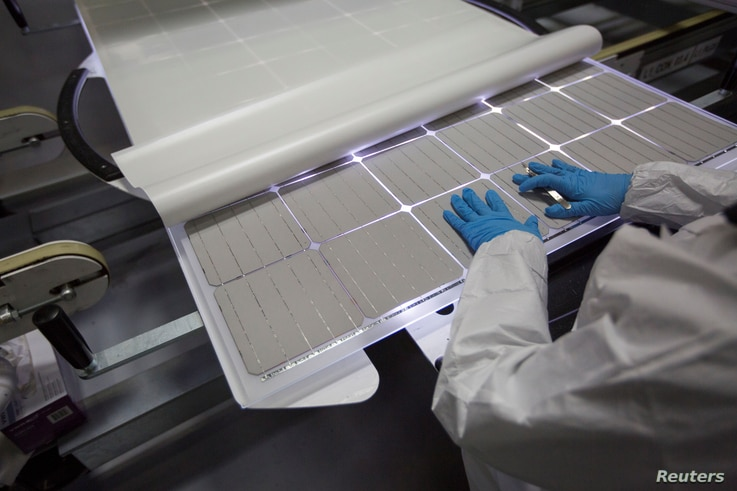 A production operator checks a panel at the SolarWorld solar panel factory in Hillsboro, Oregon, Jan. 15, 2018.