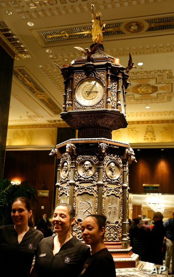 Employees of the spa at New York's renowned Waldorf Astoria pose for a photo in front of the famous clock on the hotel's first floor, Feb. 28, 2017. The bastion of gilded splendor closed March 1 for massive renovations.