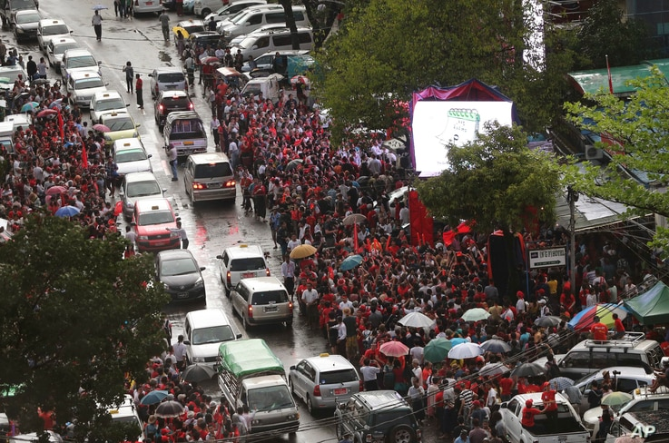Supporters of Myanmar's National League for Democracy party, gather outside the NLD headquarters in the rain in Yangon, Myanmar, Nov. 9, 2015.