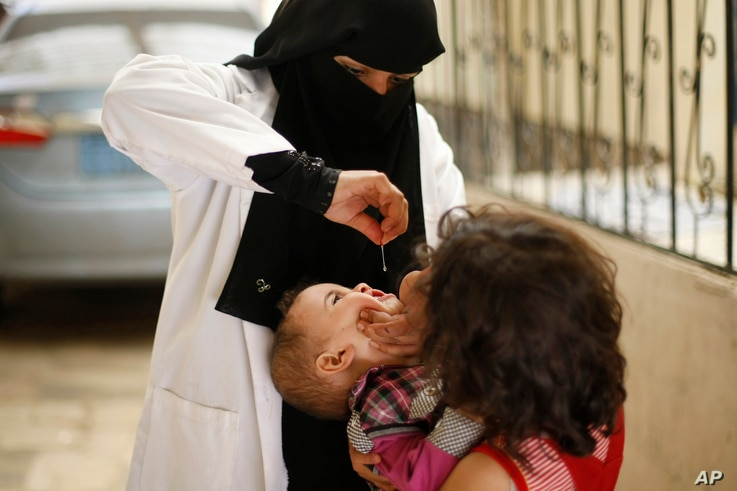 A Yemeni health worker gives the polio vaccine to a child during a house-to-house polio immunization campaign in Sanaa, Yemen, Tuesday, Aug. 12, 2014.