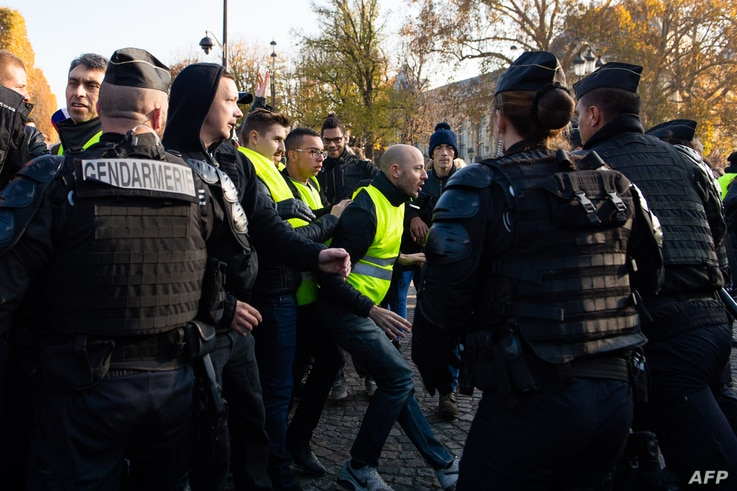 "French gendarmes face ""Yellow Vest"" protesters demonstrating on the Champs-Elysees, in Paris, France, Nov. 17, 2018,"