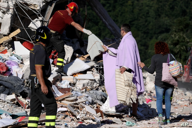 A man is given personal belongings after rescuers recovered the body of a woman from the collapsed house, in Amatrice, Aug. 26, 2016.