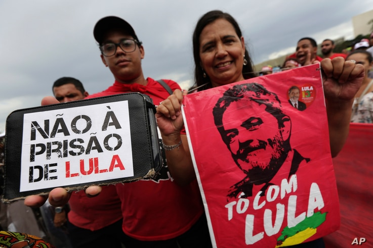 """Demonstrators carry signs written in Portuguese that read """"No Prison for Lula,"""" left, and """"I'm with Lula,"""" during a protest in support of Brazil's former President Luiz Inacio Lula da Silva, in Brasilia, Brazil, April 4, 2018."""