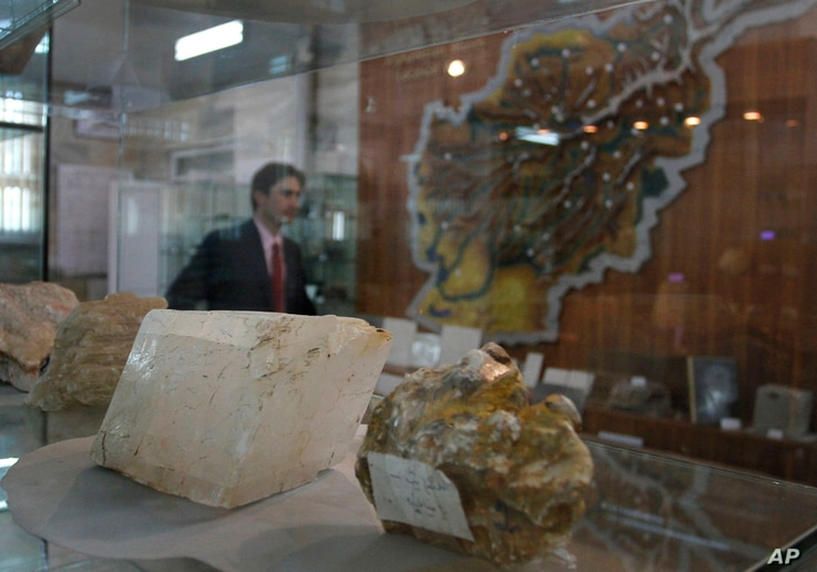 FILE - An Afghan journalist walks by precious stones on display as he attends a news conference held by the Afghan minister of mines in Kabul, June 17, 2010. A 2010 U.S. study estimated that there are more than $1 trillion worth of untapped mineral d...