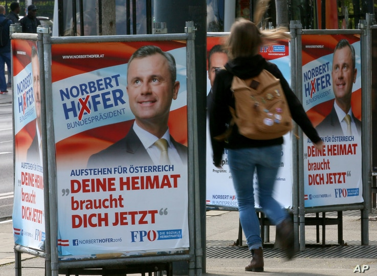 A woman walks past election posters of Norbert Hofer, candidate for presidential elections of Austria's right-wing Freedom Party, FPOE, in Vienna, Austria, April 19, 2016.