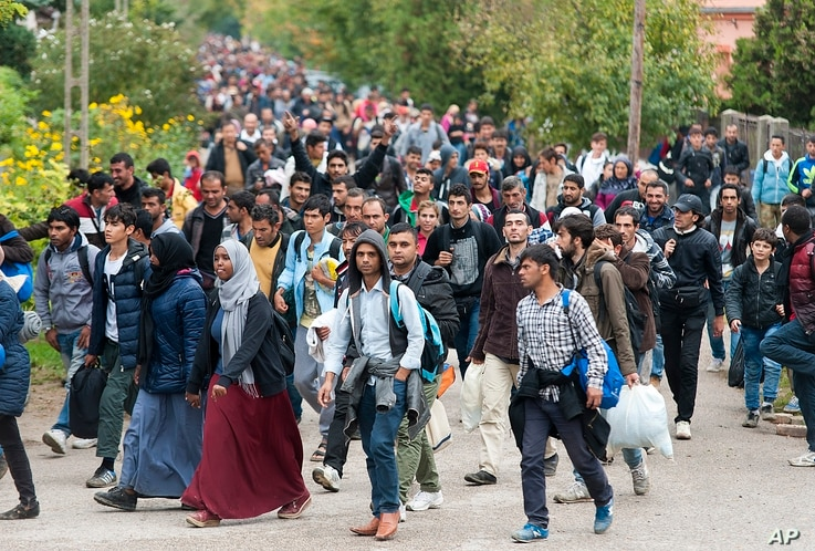 Migrants walk along a street after they arrived by train in Hegyeshalom, at the Austrian border, 169 km west of Budapest, Hungary, Oct. 7, 2015.