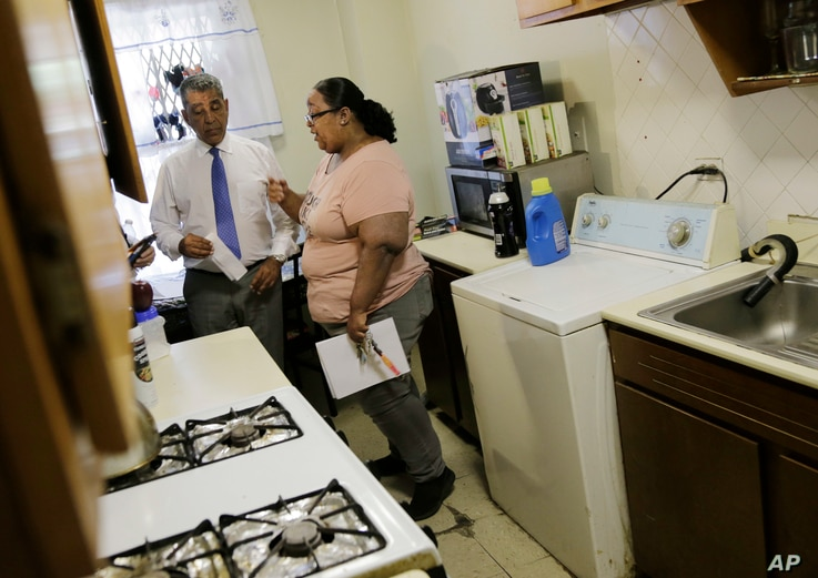 FILE - Jennifer Gomez talks with U.S. Rep. Adriano Espaillat about repairs needed in her apartment in public housing in New York, July 3, 2018.