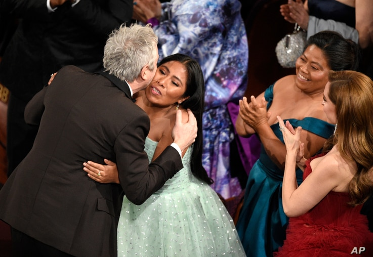 """Yalitza Aparicio, right, congratulates Alfonso Cuaron in the audience as he is announced the winner of the award for best cinematography for """"Roma"""" at the Oscars on Sunday, Feb. 24, 2019, at the Dolby Theatre in Los Angeles."""