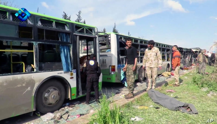 This frame grab from video provided by the Thiqa News Agency, shows rebel gunmen stand at the site of a blast that damaged several buses carrying evacuees, at the Rashideen area, outside Aleppo, Syria, April. 15, 2017.