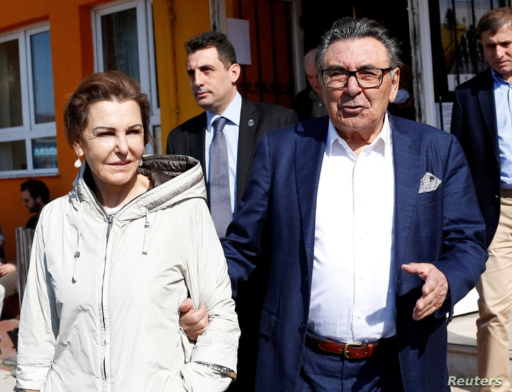 FILE - Aydin Dogan, founder and honorary president of Dogan Holding, and his wife, Sema Dogan, leave a polling station during a referendum in Istanbul, April 16, 2017.