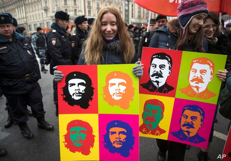 Communist party supporters carry Andy Warhol-style portraits of Cuban Revolution hero Ernesto 'Che' Guevara, center, and Soviet leader Josef Stalin, right, during a demonstration marking the 100th anniversary of the 1917 Bolshevik revolution in Mosco...