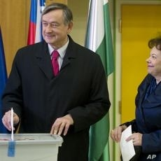 Slovenia's president Danilo Turk, left, casts his ballot as his wife Barbara Miklic, right, looks on at a polling station in Ljubljana, December 4, 2011.