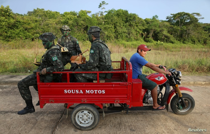 Brazilian army forces soldiers take a ride at the border of Brazil with Colombia during a training which aims to increase the security along borders, in Vila Bittencourt, Amazon State, Brazil, Jan. 18, 2017.