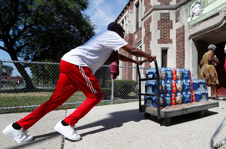 Teacher Cedric Cook pushes cases of water into Noble School in Detroit, Sept. 4, 2018. Some 50,000 Detroit public school students began the school year last month by drinking water from coolers, not fountains, after the discovery of elevated levels o...