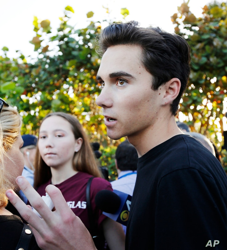 Marjory Stoneman Douglas High School student David Hogg, left, walks to class for the first time since a former student opened fire there with an assault weapon in Parkland, Florida, Feb. 28, 2018.