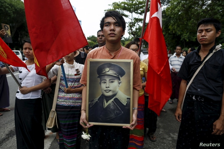 People hold General Aung San's portrait as they wait to pay respect during an event marking the anniversary of Martyrs' Day outside the Ministers' Building, formerly known as the Secretariat building, where General Aung San and eight others were assa...