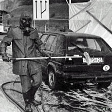 A 1986 file photo shows firefighters in protective gear washing a West German car near Herleshausen at the East German border after it arrived from Poland bearing radioactive fallout from the Chernobyl nuclear plant disaster